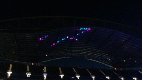 Lasers play psychedelically on the stadium roof.